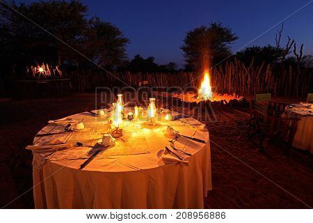 Nighttime campfire and decorated table for outdoor safari catering