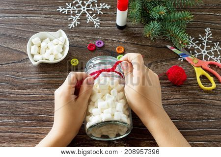 A Child Knots A Scarf With Details Of A Christmas Gift With A Snowman Sweets. Made By Own Hands. Chi