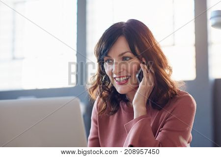 Attractive young businesswoman smiling while sitting alone at her desk in a modern office talking on a cellphone and using a digital tablet