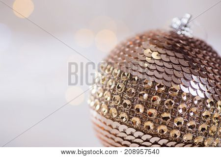 Glowing Christmas Ball Of Metallic Color With Sequins And Rhinestones On Light Bokeh Background