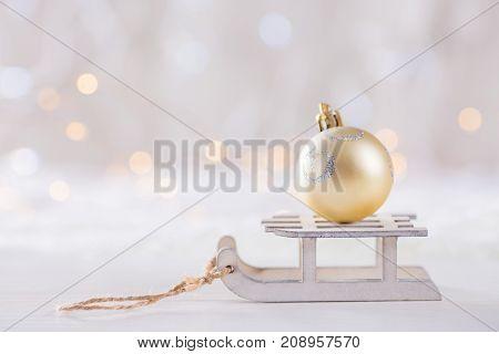 Shining Christmas Ball On Toy White Sled On Light Bokeh Background