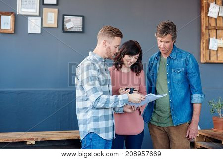 Three casually dressed young work coworkers discussing paperwork while standing together in a large modern office