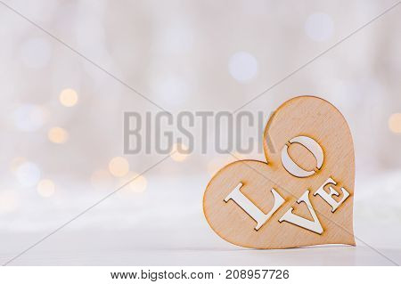 Wooden Heart With Inscription Love On Light Bokeh Background