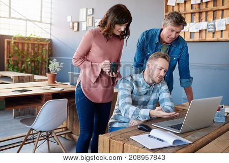 Three casually dressed young businesspeople working on a laptop and talking together while standing at a table in a modern office