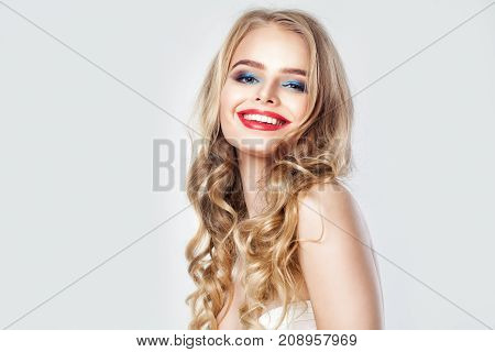 Happy Smiling Woman Fashion Model. Pretty Female Face with Blonde Curly Hair Makeup and Cute Smile on Banner Background with Copy space