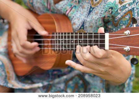 Young hipster woman playing on Ukulele outdoors.