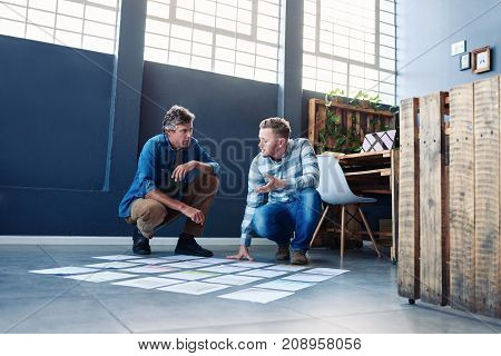 Two focused young office colleagues brainstorming together while crouching over papers spread out in a square on the floor of a modern office