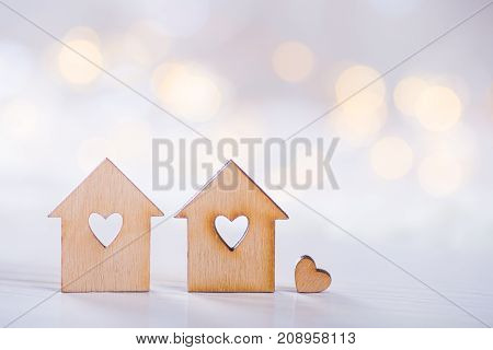 Two Wooden Houses With Hole In The Form Of Heart With Little Heart On Light Bokeh Background
