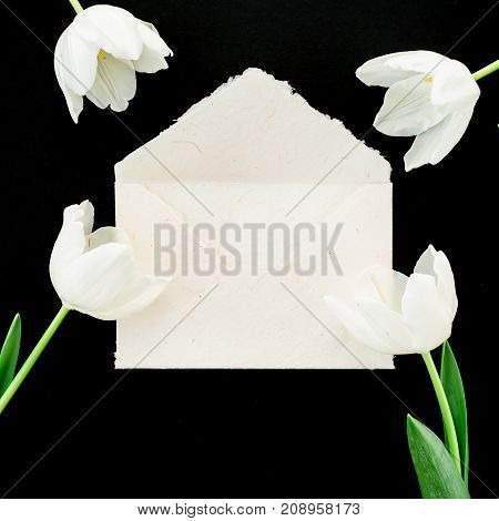 Tulip flowers and paper envelope on black background. Flat lay, Top view