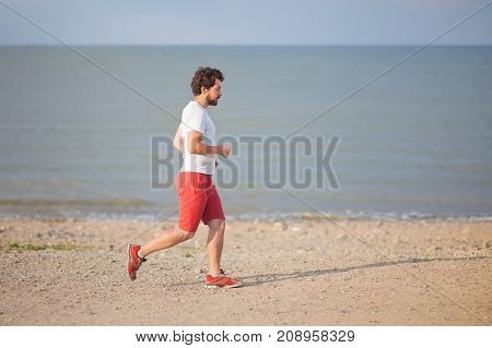 Handsome man running on the beach morning exercise.