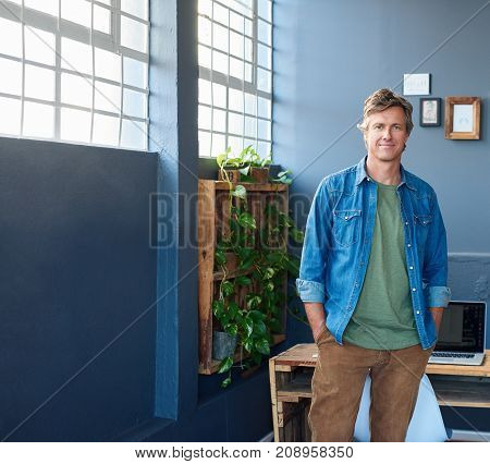 Portrait of a casually dressed business professional smiling confidently while standing with his hands in his pockets in a bright modern office