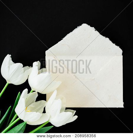 White tulip flowers and vintage envelope on black background. Flat lay, Top view