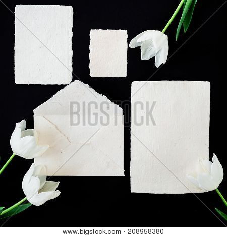 Paper envelop with white cards and flowers. Flat lay, top view, isolated on background