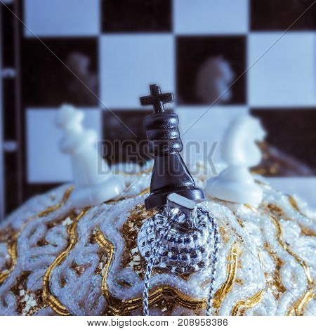 chess pieces stand on a Christmas toy on a background of a game board in which are reflected