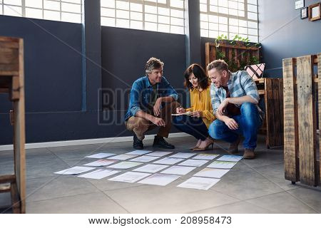 Three smiling young office colleagues brainstorming together while crouching over papers spread out on the floor of a modern office