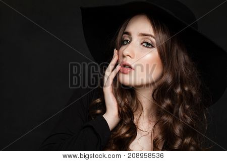 Beautiful Fashion Model Woman with Perfect Wavy Hair and Makeup. Young Model in Black Hat