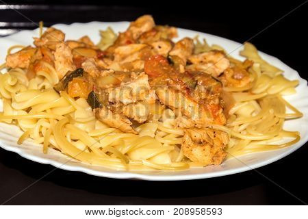 Natural chicken grilled meat with pasta with tomato sauce.