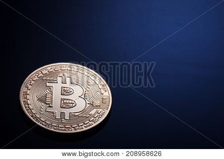 Golden bitcoin on a dark blue background. The concept of virtual business and currency.