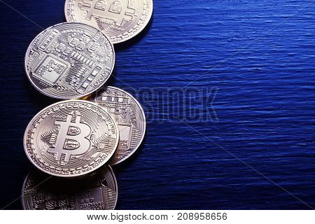 Golden bitcoins on a textured wooden background. The concept of virtual business and currency.