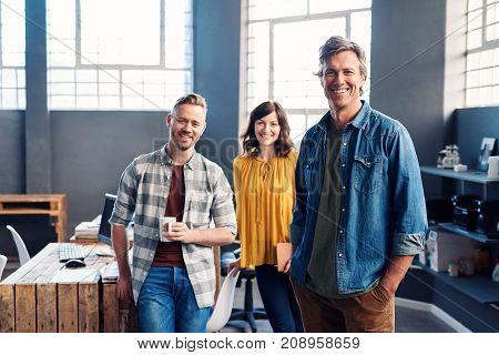 Portrait of three casually dressed young office colleagues smiling confidently while standing together in a large modern office