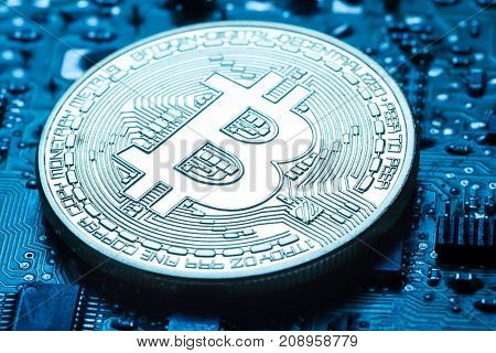 Virtual currency is the golden bitcoin on the background of the printed circuit board. Toning. The concept of virtual money and crypto currency.