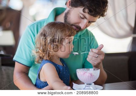 Father feeding llittle girl with ice cream indoors. Family lifestyle.