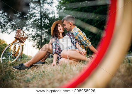 Love couple with vintage bikes sitting on grass