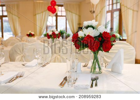 Beautifully set festive table decorated with a bouquet of roses. The preparations for the party
