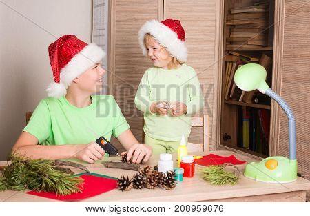 Children in Santa hats making Christmas decorations. Make christmas decoration with your own hands. Handcraft concept.