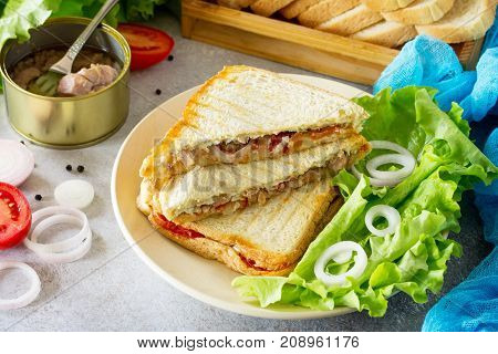 Double Sandwich With Canned Tuna And Feta Cheese Served With Lettuce Leaves On A Background Of Gray