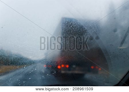 Rain drops on windscreen and blurred truck in forest road. Overtaking of the truck. Low visibility. Concept of road danger bad weather.