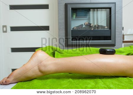 Woman Having Legs Massage With Hot Stones