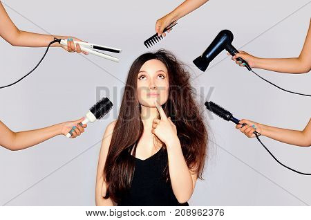 Young woman getting a beauty and hair style in the same time with hands making different works. Damaged hair long. Styling of disobedient hair. Close-up portrait on gray background.