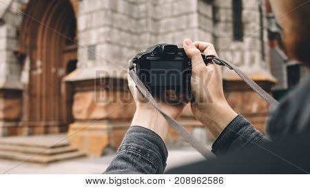 A picture of a cool and good camera. It is in the guy's hands. He is holding the camera like that because he wants to take a picture of the church. Close up. Cut view