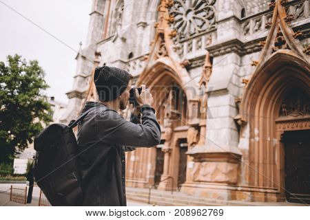 Nice shot of a guy taking pictures of old brown church. He is standing besides it on the street. He has never seen such a beautiful building before. Cut view