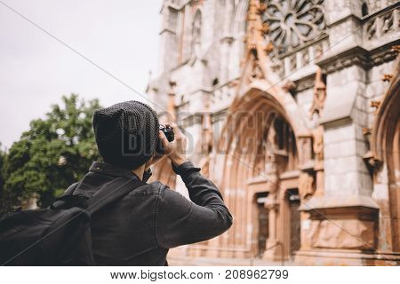 Another picture of a young traveller that likes to take pictures of old buildings in different cities. This time he is shooting the brown gothic church. Close up. Cut view