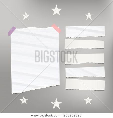 White ripped lined note, notebook paper for message or text stuck with sticky tape on gray background with stars