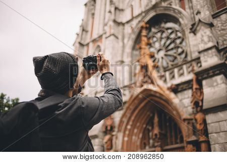 Cut picture of a young traveller that likes shooting It is shown that the guy is shooting nice and brown catholic church building. Close up. Cut view
