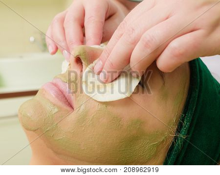 Beautician Wiping Off Green Mask On Woman