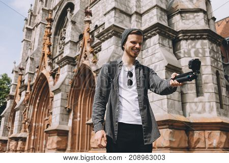 Cheerful cool and nice traveller is taking a selfie. Besides him there is a big great church building. Young man is smiling. He looks happy.