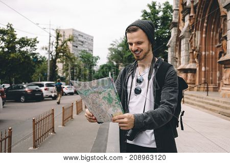 Curious and ambitious young tourist is standin on the street and holding a city map in his hands. He has found the adress of place where he wants to go so that's why he is smiling.