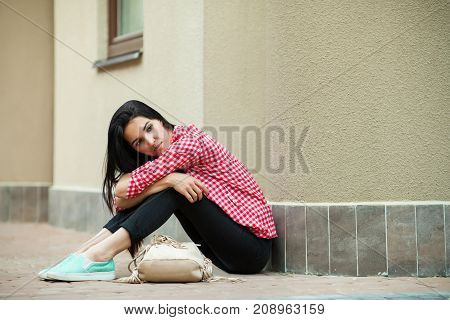 pretty young girl sitting on ground near building, gorgeous woman in pink jacket and black pants with bag relaxing outdoor