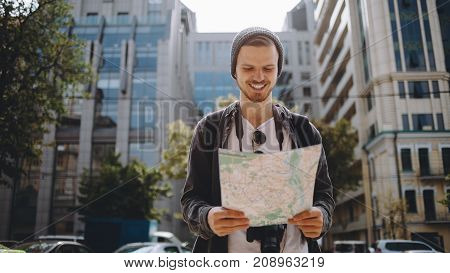 Beautiful and sunny picture of a handsome awesome guy standing outside on the street and looking to the map. There is a big building behind him. Young man has found a place to go so he is happy about that. Close up