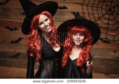 Halloween Concept - Beautiful caucasian mother and her daughter with long red hair in witch costumes and magic wand celebrating Halloween posing with over bats and spider web on Wooden studio background.