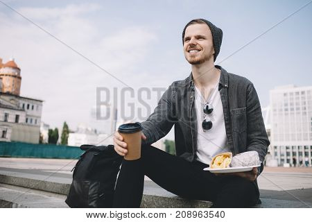 Close up of a tourist that had a long trip. Now he wants to have some rest and eat his meal. So in the right hand there is a cup of hot coffee. In the left hand there is a plate with french fries and burger. This meal is tasty and yummy. Cut view