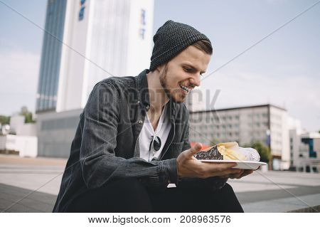Hungry tourist is sitting on the steps and holding a plate with tasty meal. Unfortunately this meal is junk food but it tastes so good. Young man cant' wait to eat it. Close up