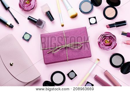 Gift box, pink purse and decorative cosmetics on pastel background, top view