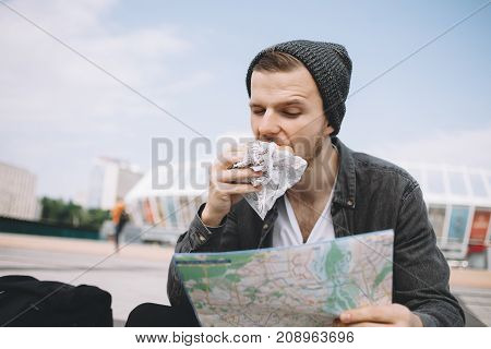 Good-looking and attracive tourist is sitting on the big white steps. He is eating a burger with his right hand and looking to the map which he is holding with his left hand. He is searching an interesting place to visit. Close up. Cut view