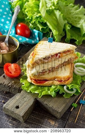 Double Sandwich With Canned Tuna And Feta Cheese Served With Lettuce Leaves On A Wooden Cutting Boar