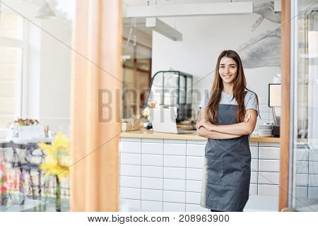 Young lady entrepreneur running a successful small cafe. Standing in front of coffee machine with arms crossed.